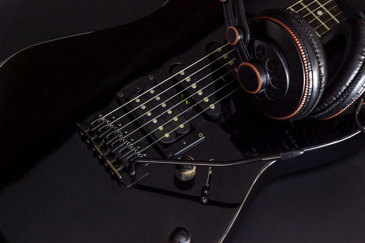 Close-Up Of Guitar And Headphones Against Black Background