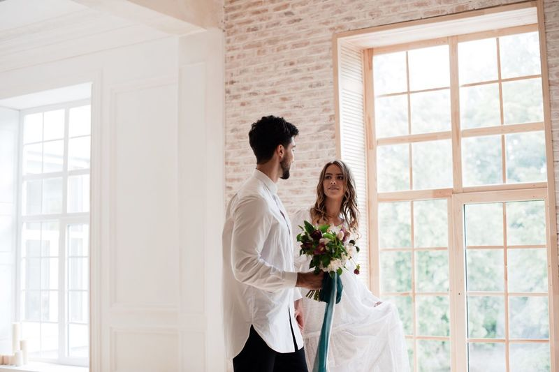 Groom holding flower bouquet with bride standing by window at home