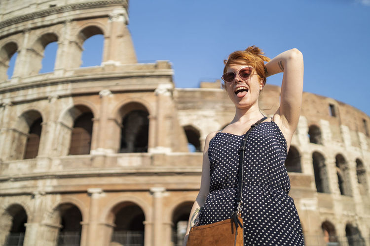 Portrait of young woman standing against historic building