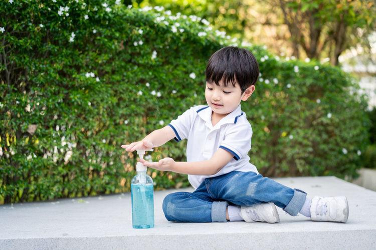 Cute boy applying sanitizer against plants