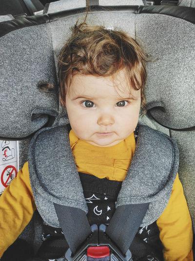 High angle portrait of cute boy sitting in car
