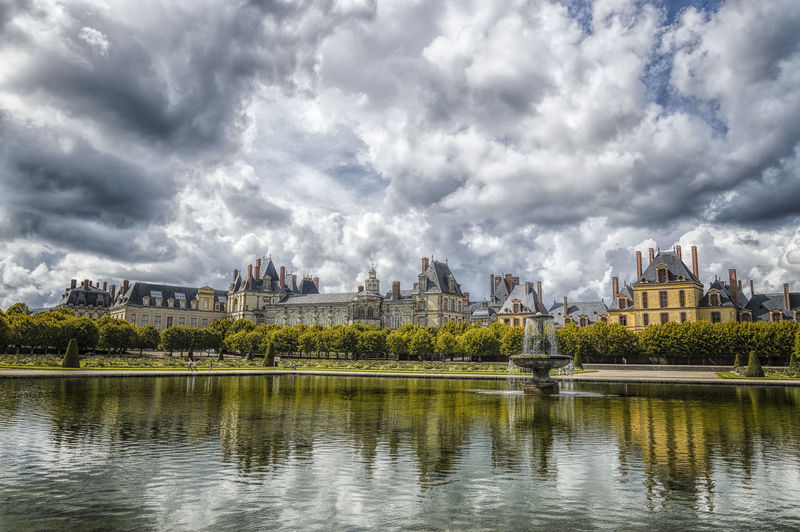 Fontainbleau reflecting in pond against cloudy sky
