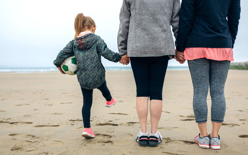Rear view of family holding hands at beach