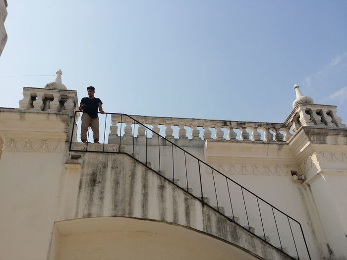 Low Angle View Of Man Standing By Railing On Building Against Sky