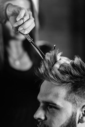 Close-up of woman cutting man hair at shop