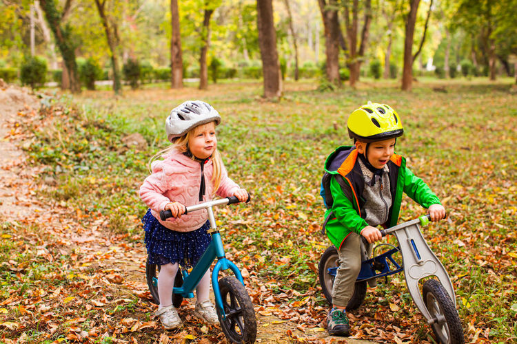 Siblings riding bicycle on autumn leaves