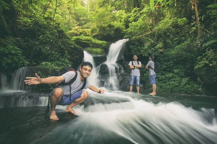 Beautiful waterfall in green forest in jungle. Be. Ready. Beauty In Nature Blurred Motion Casual Clothing Cheerful Day Enjoyment Flowing Water Forest Full Length Fun Happiness Leisure Activity Lifestyles Long Exposure Motion Nature Outdoors Real People River Smiling Togetherness Tree Water Waterfall