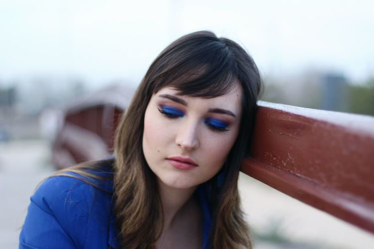 Thoughtful woman with eye make-up leaning on railing