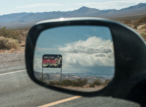 Welcome to... California Close-up Day Death Valley Desert Journey Land Vehicle Landscape Mode Of Transport Mountain Mountain Range Nature Nevada No People Non-urban Scene Outdoors Rear View Mirror Reflection Road Road Sign Side-view Mirror Signs Solitude Transportation Travel