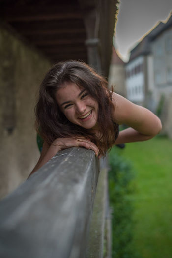Portrait Of Cheerful Young Woman Leaning On Railing