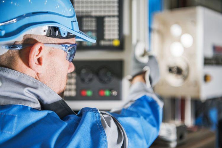 Close-up of man using machinery at factory