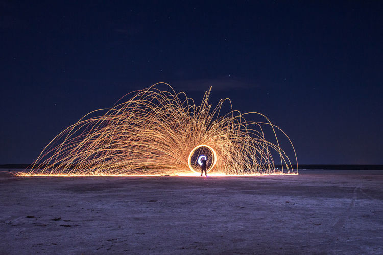 Man with illuminated wire wool on field against sky