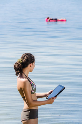 Portrait of young women standing in Lake Constance with digital tablet in her hand and another person on air mattress in the background EyeEmNewHere Lake Constance Adult Air Mattress Bikini Communication Connection Day Digital Tablet Focus On Foreground Holding Leisure Activity Lifestyles Nature Outdoors Purple Real People Sea Standing Technology Water Wireless Technology Women Young Adult