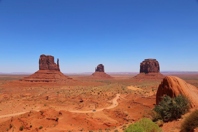 Rock formations in desert at monument valley against clear blue sky