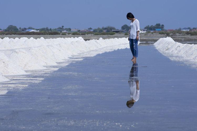 Woman standing on salt flat against clear sky