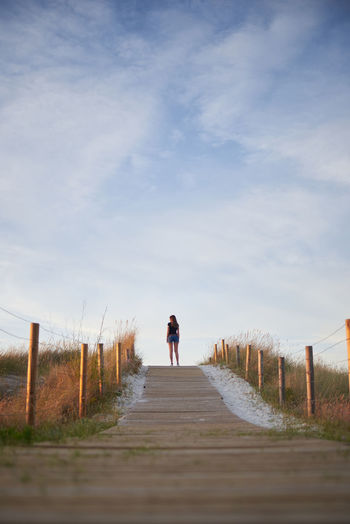 Rear view of woman standing on footpath against sky