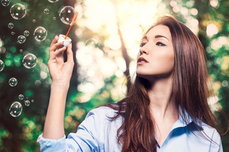 Beautiful woman holding bubble wand against trees