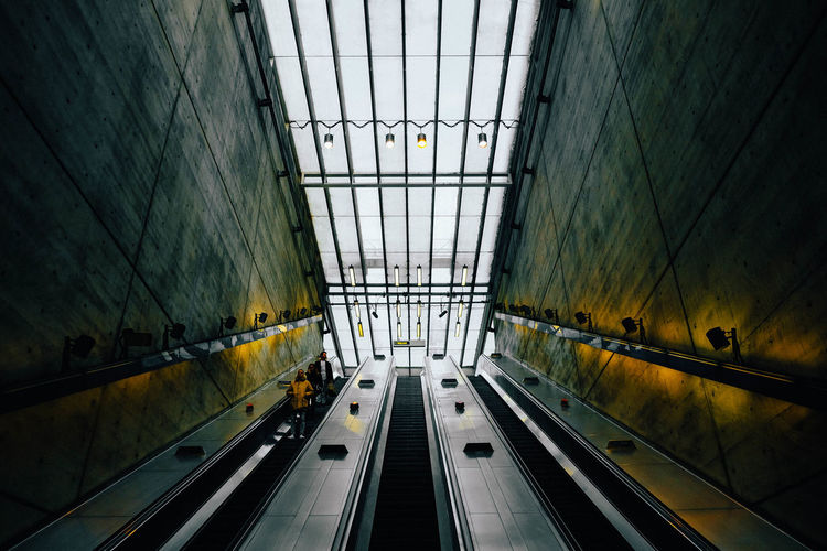 Low angle view of people on escalators in subway station
