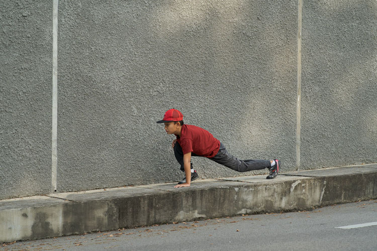 Full length of boy exercising on footpath