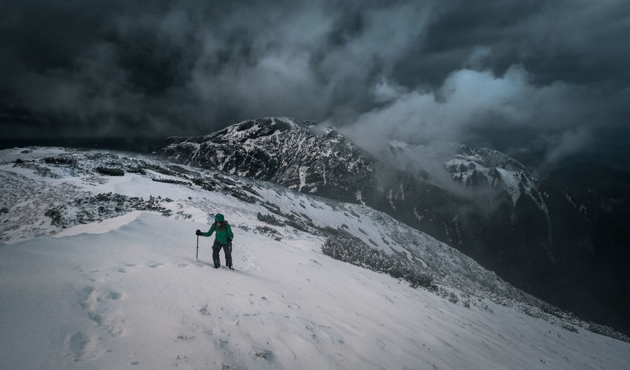 Woman hiking on snowcapped mountain during storm cloud