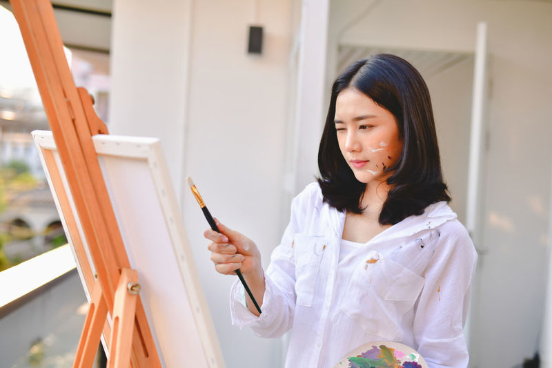 Young woman painting while standing outdoors