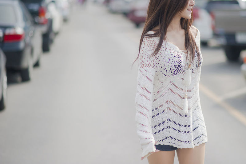 Midsection of young woman standing at parking lot