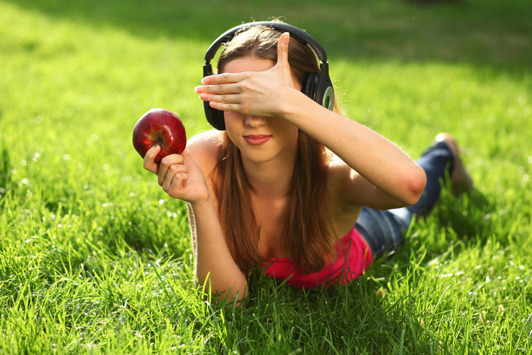Woman with headphones listening music on the grass Beautiful Woman Outdoors Hairstyle Day Real People Land Lying Down Healthy Eating Fruit Nature Apple - Fruit Women Food Lifestyles Field Food And Drink Leisure Activity Plant Young Women Young Adult Grass One Person Green Color