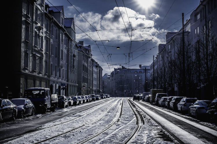 Railroad Track Amidst Parked Vehicles In City During Winter
