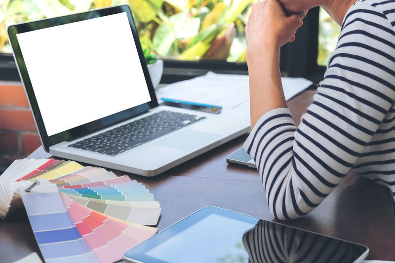 Midsection of businesswoman using laptop by color swatches in office