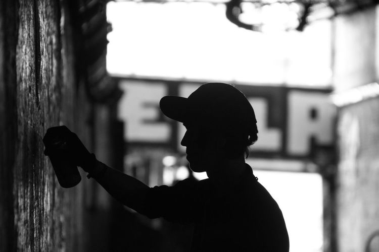 Side View Of A Silhouette Man With Spray Can