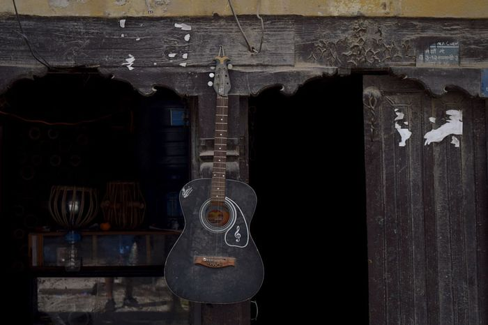 A black guitar hanging on the front of one of the many local stores in Katmandu's Thamel. Nepal Thamel Thamel Street Store No People Indoors  Day Close-up ArtWork