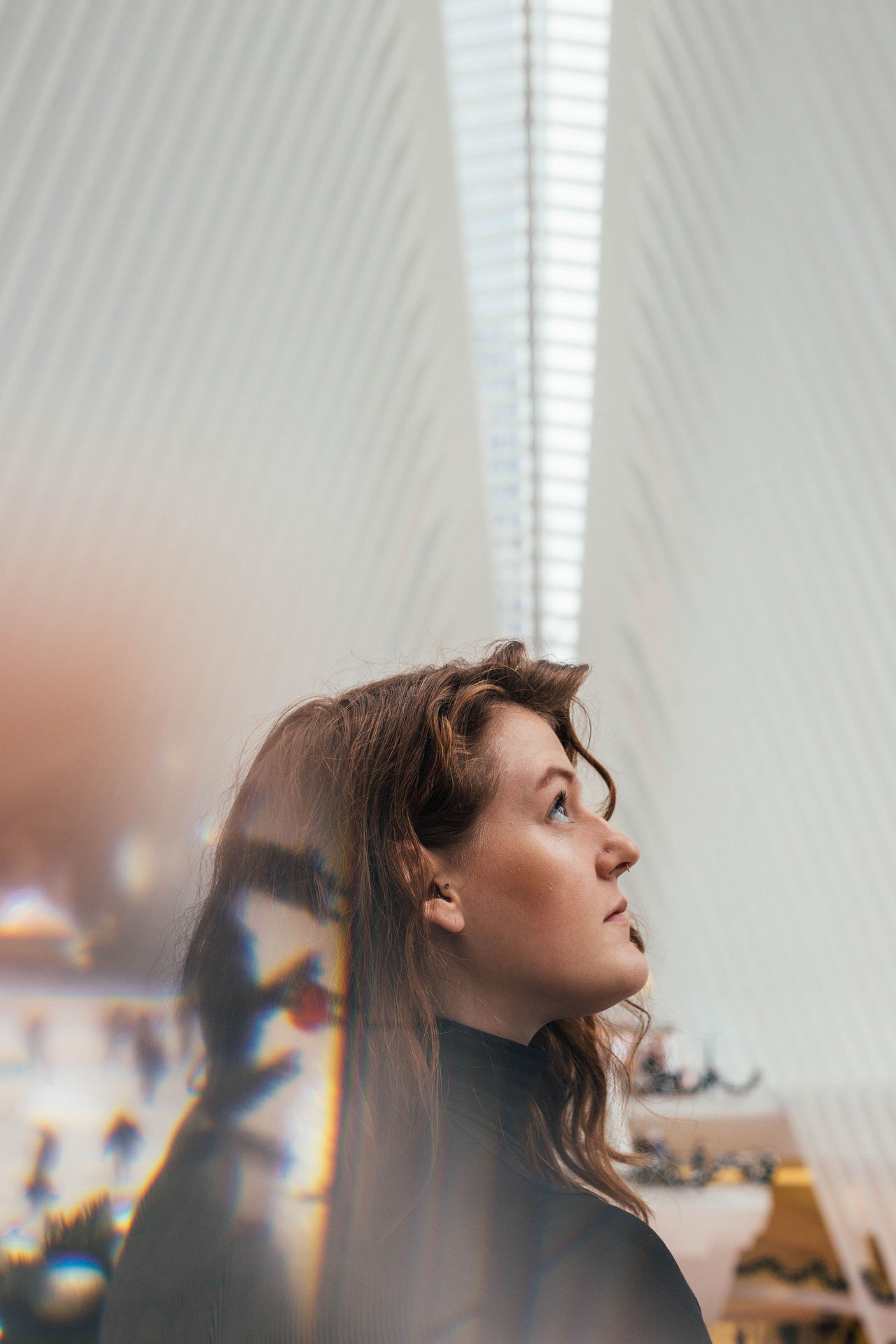 Close-up of thoughtful young woman with long brown hair against ceiling