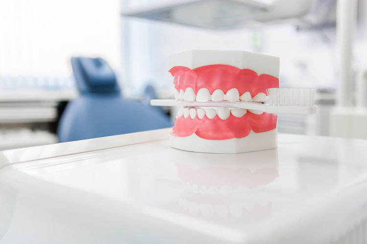 Close-up of dentures with toothbrush on table
