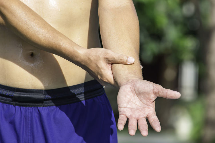 The hand grips the arm that inflammation from a sports injury. Acute Adult Anatomy Arm Background Body Care Caucasian Chronic  Closeup Color Cramp Gripping Hand Health Holding Human Hurt Ill Illness Inflammation Injured Injury Leg Massage Massaging Medical Medicine Men Mid Muscle Outdoors Overeating Pain Painful People Physical Red Repetitive Shoulder Skin SORE Stomachache Stress Suffering Syndrome Tension Touch Uncomfortable Unwell