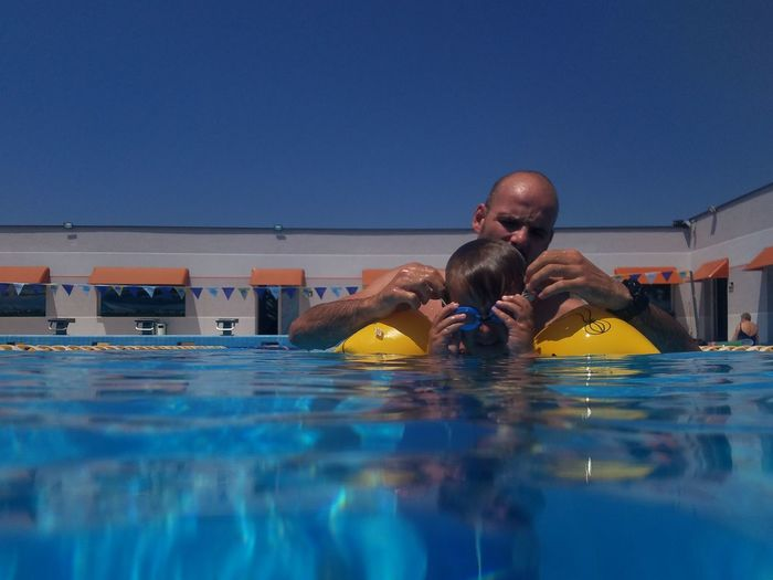 Father and son swimming in pool against clear blue sky