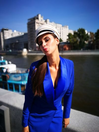 Portrait of young woman puckering lips while standing against river in city