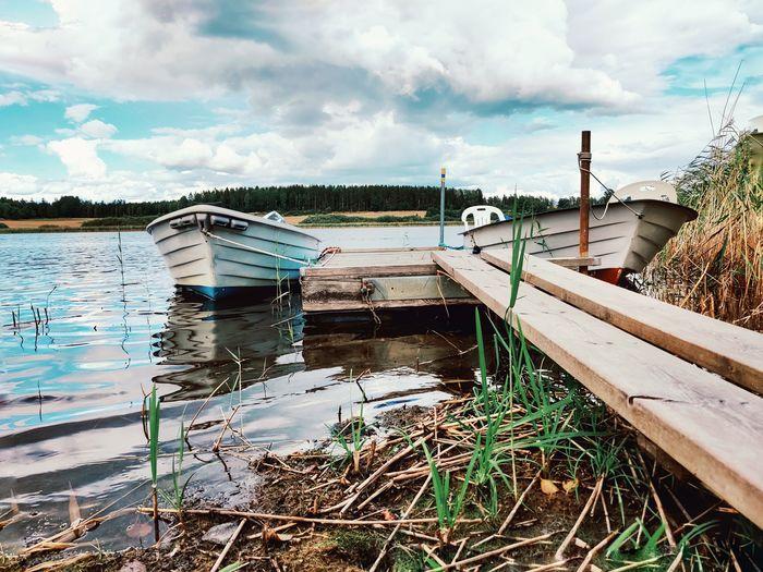 Abandoned boat moored on lake against sky