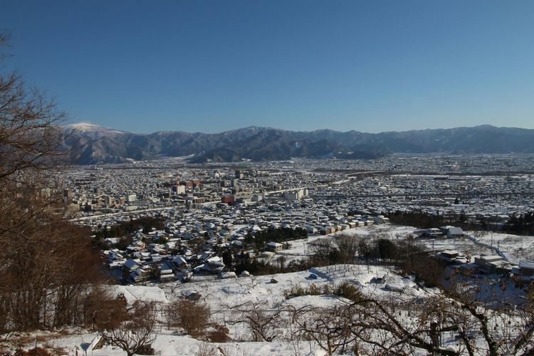 Human Settlement By Mountains Against Clear Blue Sky During Winter