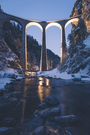 Low angle view of bridge over river at dusk during winter