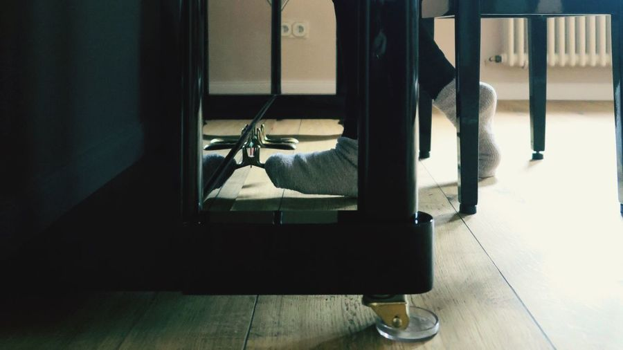 Low section of person wearing socks on floor at home