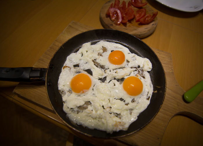 High Angle View Of Fried Egg In Frying Pan On Cutting Board At Home