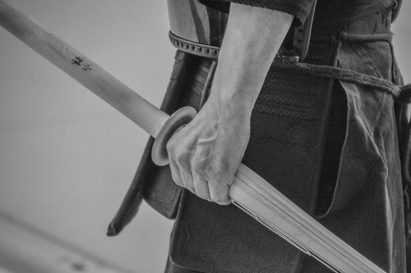 Japanese Man Holding Kendo Sword In His Hand (Black And White) Japan Japanese  Kendo Martial Arts Art Black And White Budo Budokan Close-up Focus On Foreground Human Hand Indoors  Kendoka Midsection One Person Real People Standing Sword Wooden