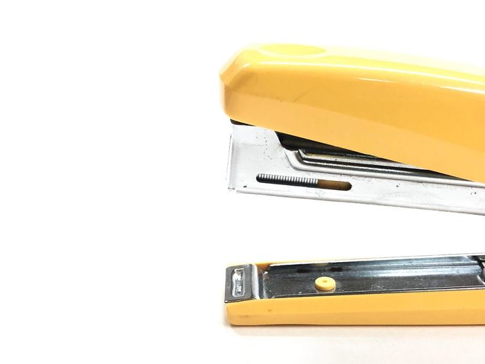 A part of yellow stapler with slightly shadow on white background. Office Supply Stationary Yellow White Background Cut Out No People Copy Space Indoors  Close-up Studio Shot Metal Still Life Single Object