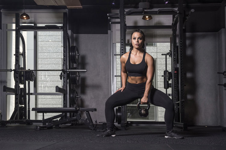Young Woman Practicing Squat Exercise With Kettlebell At Gym