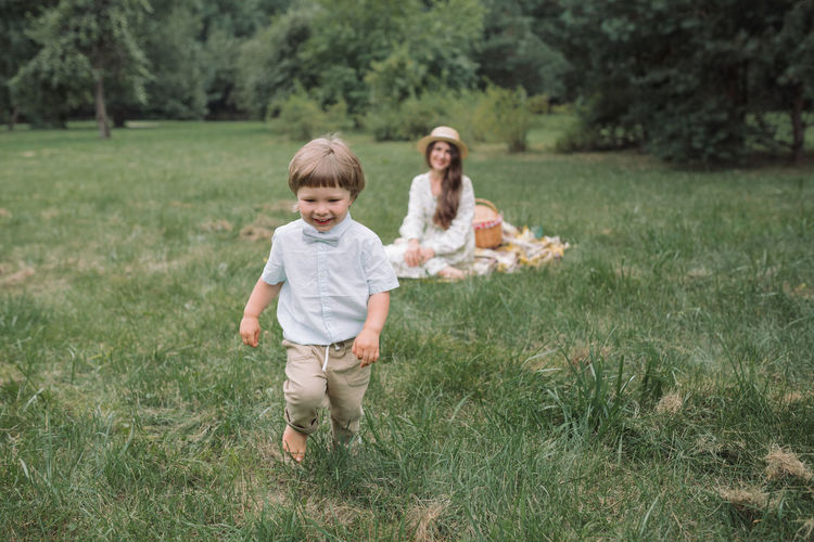 Full length of mother and daughter on grassy field
