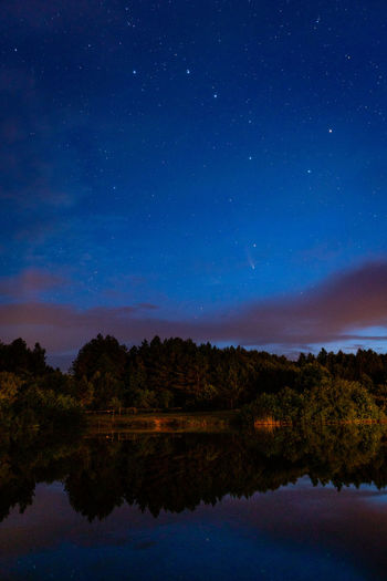 The constellation ursa major and a starry sky in the clouds and a comet over a forest lake.