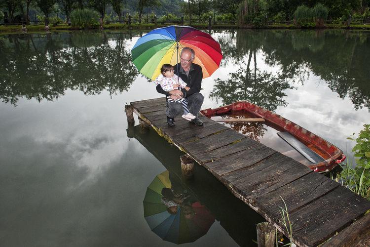Man with umbrella on lake during rainy season