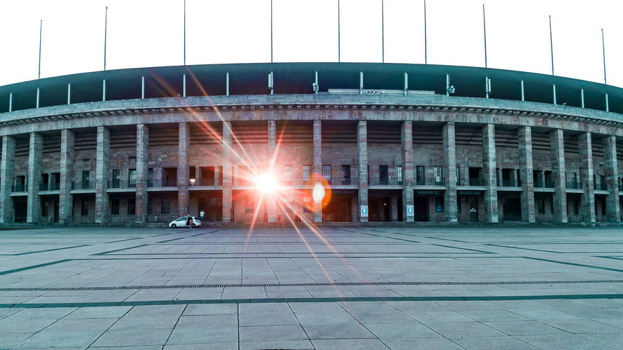 Sunset through the stadium Berlin Olympiastadion Berlin Olympic Stadium History Historic Historical Building Sunset Coral Colored Last Light Of Day Sunrays Light Lens Flare Light Through The Window 1930s Germany Dusk Dusk In The City Stadium Sport City Hockey Illuminated Soccer Architecture Sky Destruction Decline Evening Silhouette Shining Sunbeam