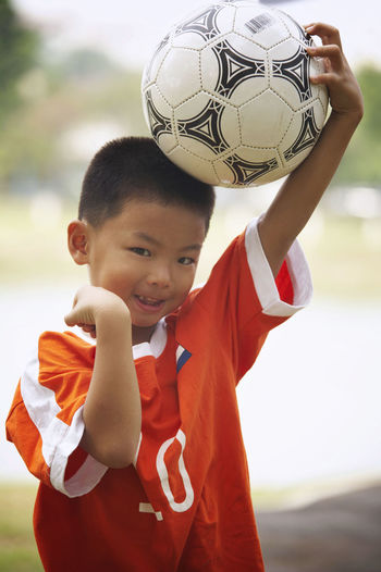 Portrait Of Confident Boy With Soccer Ball Gesturing On Field At Park