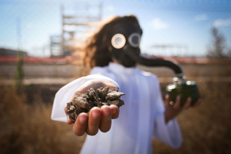 Girl wearing gas mask while holding stones on field